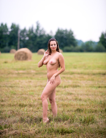 Romantic image of young naked woman posing outdoors. Sexy brunette enjoying summer time in hot day