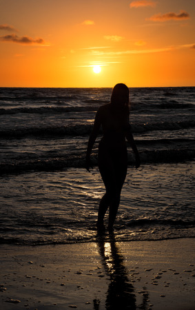 Silhouette of beautiful naked young woman posing in the sea. Sexy nude enjoying summertime at the beach at sunset