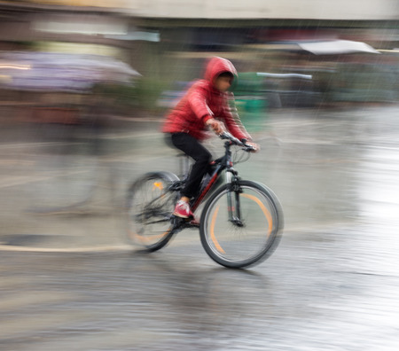 Cyclist on the city roadway on a rainy day in motion blur