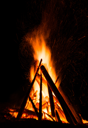 Big bonfire against dark night sky. Fire flames on black background
