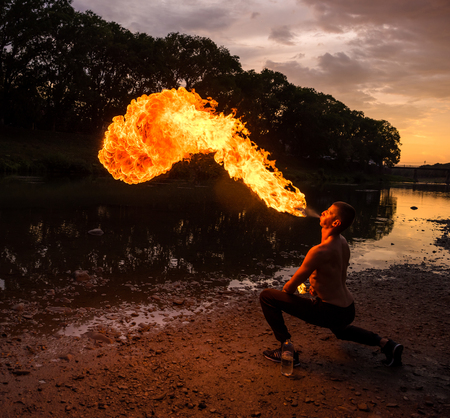 Man fire-eater blowing a large flame from his mouth