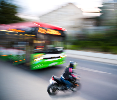 Dangerous city traffic situation with a motorcyclist and a bus in motion blur. Intentional motion blur Imagens