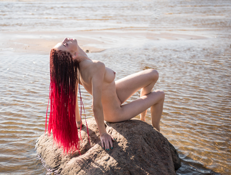 Beautiful naked young woman posing in the sea. Sexy nude redhead enjoying summertime at the beach Фото со стока