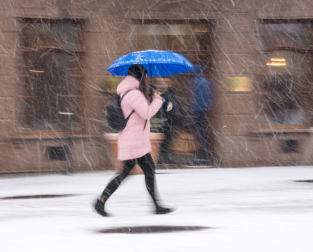 Woman with umbrella walking down the street in winter day in motion blur. Defocused image Imagens - 120419528