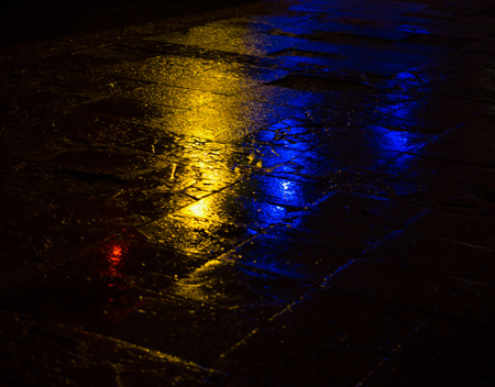 Abstract urban background. Lights and shadows of the city. Streets after rain with reflections on wet asphalt