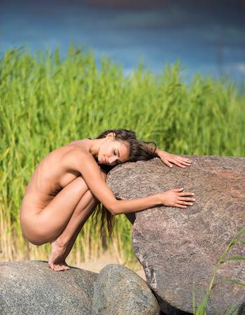 Young beautiful naked woman enjoying summer time at the beach. Sexy brunette posing on a big stone 스톡 콘텐츠