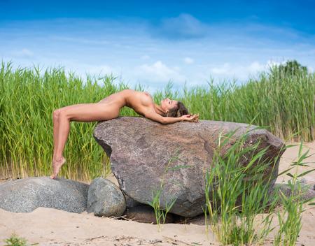 Giovane bella donna che gode dell'ora legale in spiaggia. Bruna sexy in posa su una grossa pietra