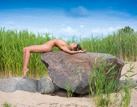 Young beautiful naked woman enjoying summer time at the beach. Sexy brunette posing on a big stone 版權商用圖片
