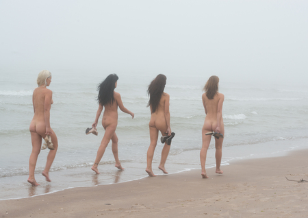 Group of beautiful young naked women posing on a foggy day. Sex nudes walking by coast Imagens