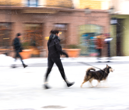 Man walking the dog on the street in snowy winter day. Intentional motion blur
