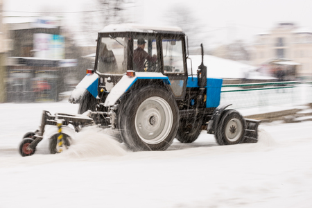 Snow removal machine cleaning the street from snow. Snowplow truck removing snow on the street after blizzard. Intentional motion blur