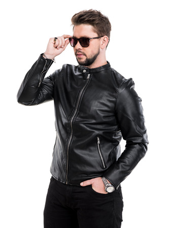 Young beard man in sunglasses wearing black leather jacket posing in studio