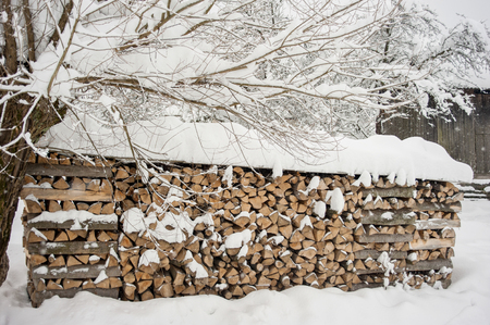 Pile of wood logs ready for winter near the house