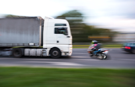 Dangerous city traffic situation with a motorcyclist and a truck in motion blur Stock Photo