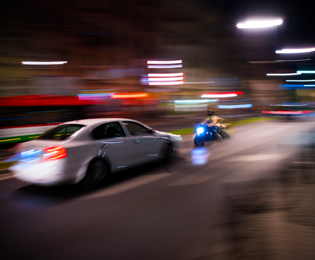 Dangerous city traffic situation with a motorcyclist and a car in motion blur at night Banco de Imagens - 120034992