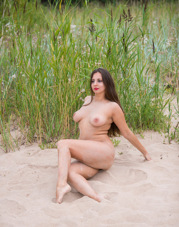 Romantic image of young nude woman posing outdoors. Sexy brunette enjoying summer time Banco de Imagens
