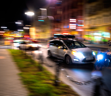 Dangerous city traffic situation with a motorcyclist and a car in motion blur at night