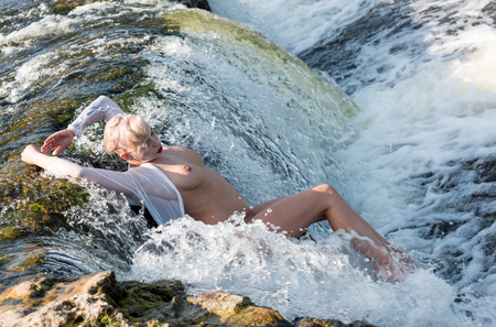Beautiful young seminude woman in white shirt enjoying summertime in the waterfall. Enjoying and relaxing in the water.Sexy blonde outdoors