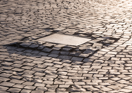 Sewer metal  hatch on pavement stone surface