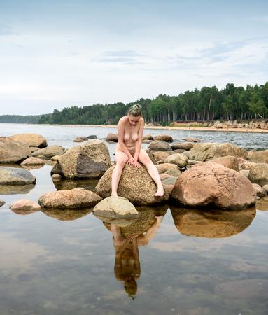 Giovane bella donna che gode dell'ora legale in spiaggia. Modella sexy in posa su pietra Archivio Fotografico