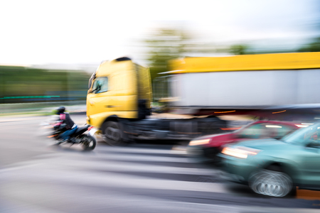 Dangerous city traffic situation with a motorcyclist and a truck in motion blur 版權商用圖片