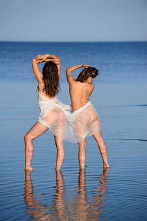 Two young nude with white shawl posing on the beach. Sexy naked brunettes enjoying summer time outdoors Stock Photo