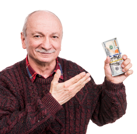Senior man holding a stack of money. Portrait of an excited old businessman. Happy old man holding dollar banknotes over white background Banco de Imagens