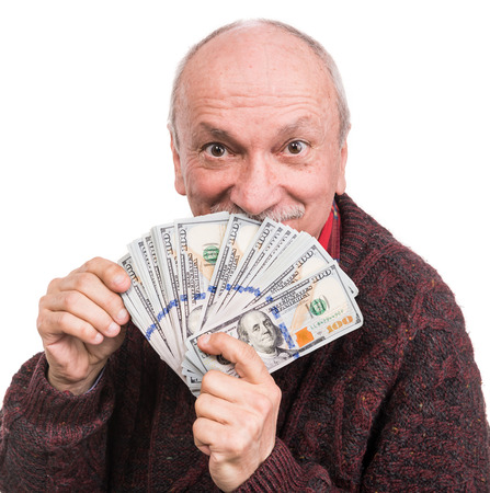 Business and finances concept. Senior man holding a stack of money. Portrait of an excited old businessman. Happy old man holding dollar banknotes over white background