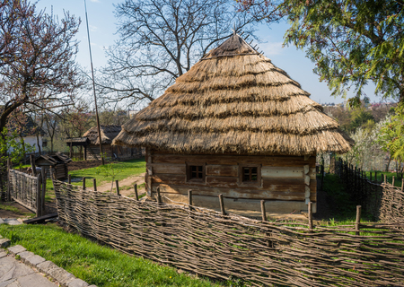 Old wooden house with  thatched roof in spring time. Museum of Folk Architecture in Uzhhorod