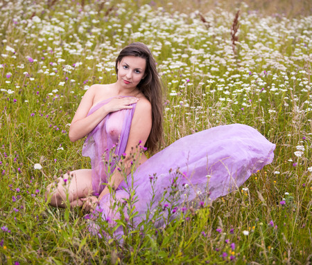 Young nude woman in pink shawl posing on the field. Sexy brunette enjoying nature and summer time outdoors 免版税图像