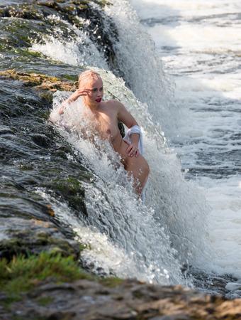 Hermosa joven semidesnuda en camisa blanca disfrutando del verano en la cascada. Disfrutando y relajándose en el agua. Sexy rubia al aire libre