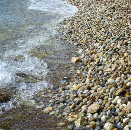 Close-up of beach pebbles. The sea wave splashing water