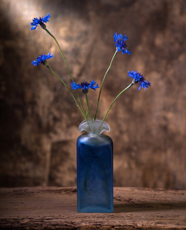 Artistic still life with beautiful blue cornflowers in vase on a wooden background