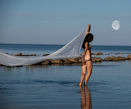 Young nude with white shawl posing on the beach in the evening. Sexy naked brunette Archivio Fotografico - 133376945