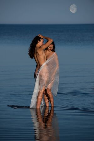Two young nude with white shawl posing on the beach in the evening. Sexy naked brunettes enjoying summer time outdoors