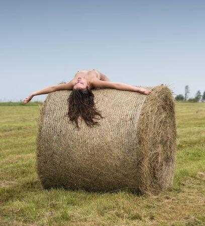 Młoda kobieta pozuje w pobliżu stogu siana na polu. Seksowna brunetka pozuje na zewnątrz