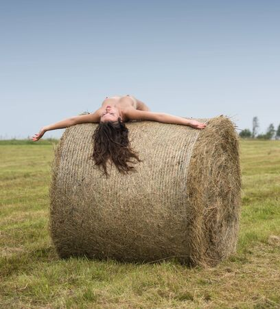 Young nude woman posing near haystack on the field. Sexy brunette posing outdoors
