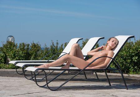 Beautiful woman sunbathing on sunbed. Enjoying summer time