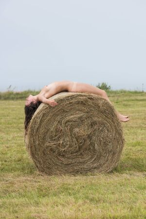 Young woman posing near haystack on the field. Sexy brunette posing outdoors Stock Photo
