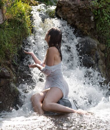 Beautiful young seminude woman in white transperent dress enjoying summertime in waterfall
