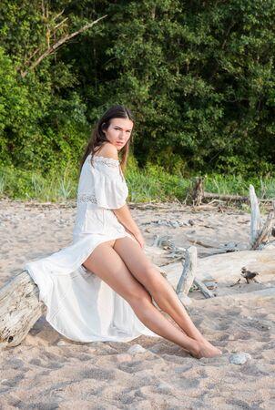 Hermosa joven semidesnuda en vestido blanco posando en la playa. Disfrutando el verano Foto de archivo
