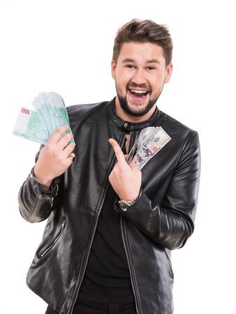 Young handsome man in black leather jacket  holding dollar and euro bills on a white background Imagens