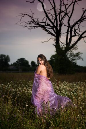 Young seminude woman in purple fabric posing outdoors. Naked woman in the evening. Sexy naked at sunset