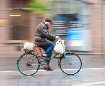 Cyclist on the city roadway in motion blur. Intentional motion blur. Defocused image Stock Photo
