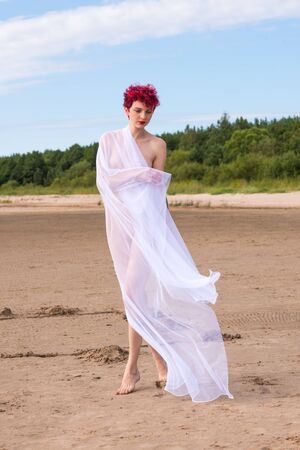Young woman posing at the beach in white veil. Sexy redhead enjoying summer time