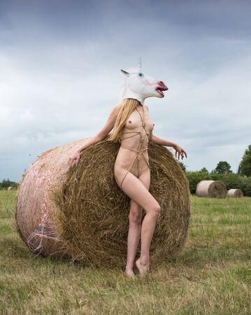 Young woman with unicorn mask on the head posing near haystack on the field. Sexy posing outdoors