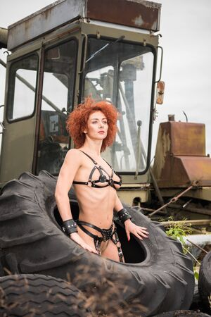 Nude redhead woman in black leather suit posing on large tractor wheels. Sexy outdoors