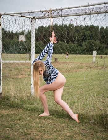 Seminude woman in a vest with tied hands posing near the football goal. Half-naked blonde outdoors