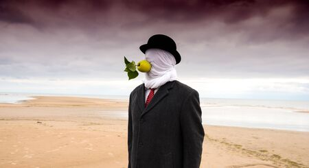 Man dressed in a black coat with closed head  and apple in his mouth posing at the beach Stok Fotoğraf
