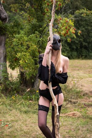Seminude woman in sexy underwear with raven mask on the head posing outdoors
